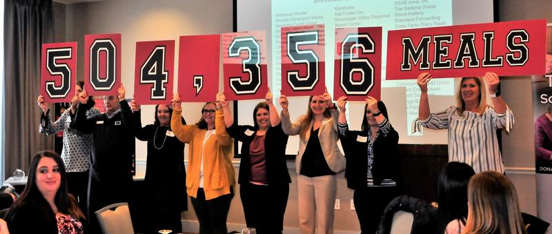 Participants in the Community Hunger Drive reveal the total.