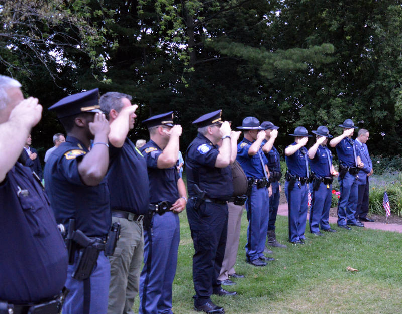 officers salute during taps