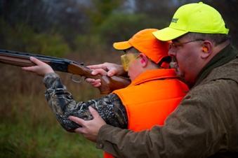 Man helps boy shoot