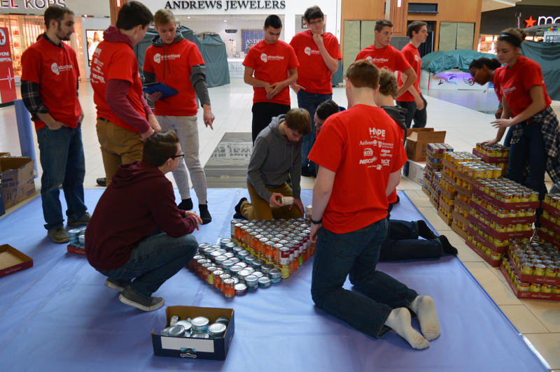 students place cans in layers to build the titanic out of cans