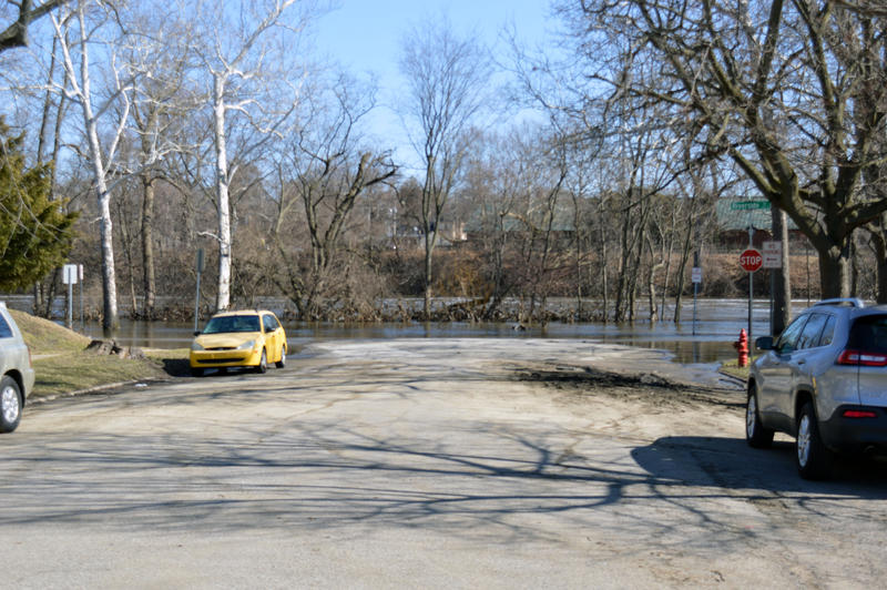 A yellow car sits on dry ground with water covering the street behind it