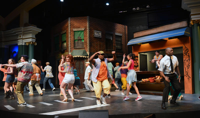 about 15 colorful people dance around a stage made to look like a New York City street corner