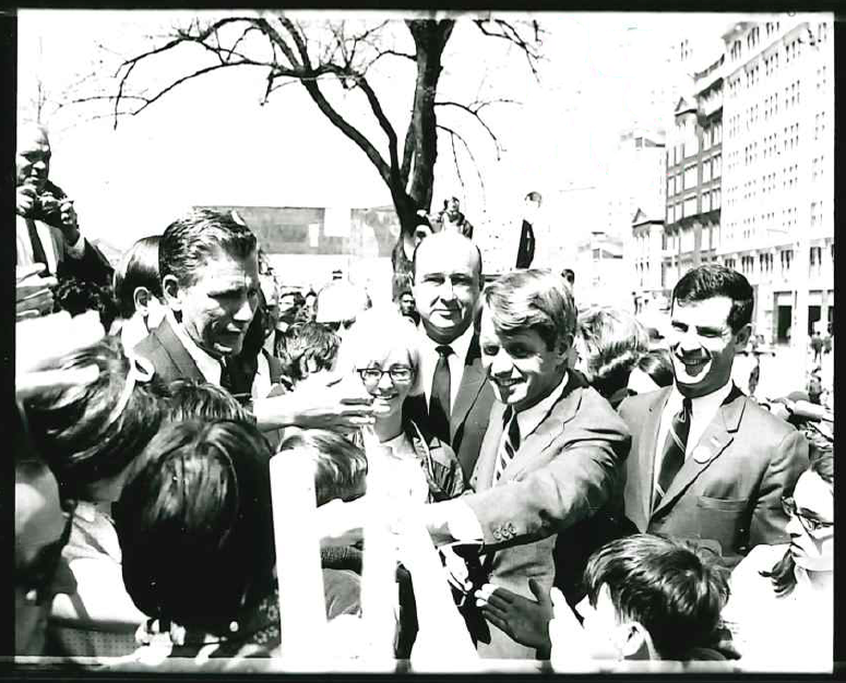 Kennedy smiles and shakes hands with enthusiastic crowds in a black and white photo