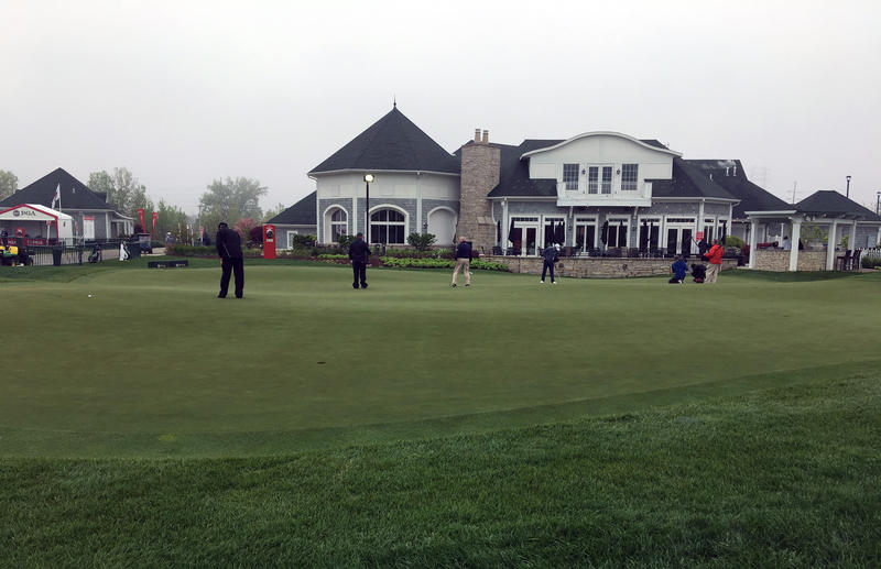 Golfers put on a practice green in front of a clubhouse building