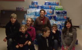Principal Virginia Lusk sits with students at Herndon Consolidated after receiving a water donation for the community.