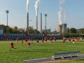 "Poca, West Virginia The Poca High School ""Dots"" practice near an American Electric Power coal-fired plant that powers nearly two million homes. Scrubbers clean some of the sulfur and mercury—but not the carbon—from the smoke."