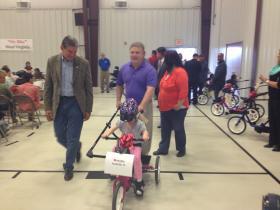 Isabella goes on the bike parade with Sen. Joe Manchin.