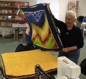 Quilt Guild Member Jane Frenke takes a quilt square from the stack for the 'parade of quilts' at a recent meeting.