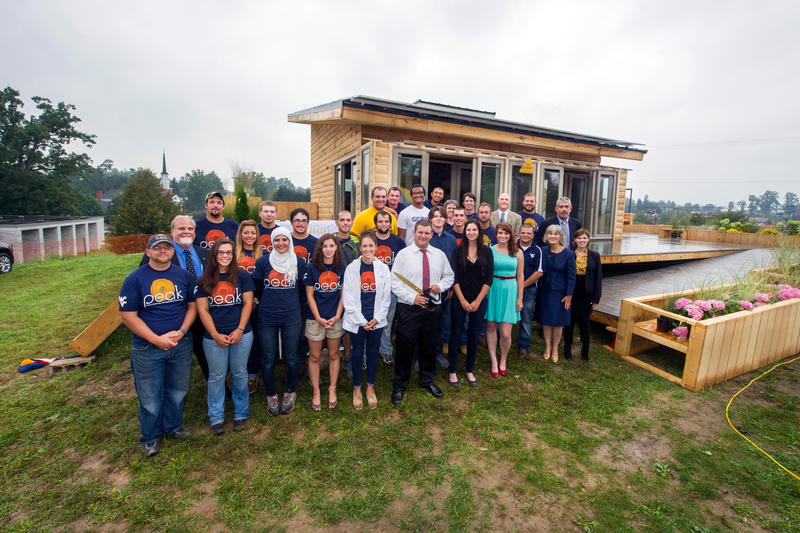 WVU's 2013 Solar Decathlon team in front of their log-cabin inspired home.