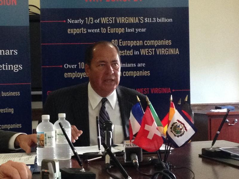 Govrnor Earl Ray Tomblin sitting in front of a blue background at a table with small, international flags in front of him.