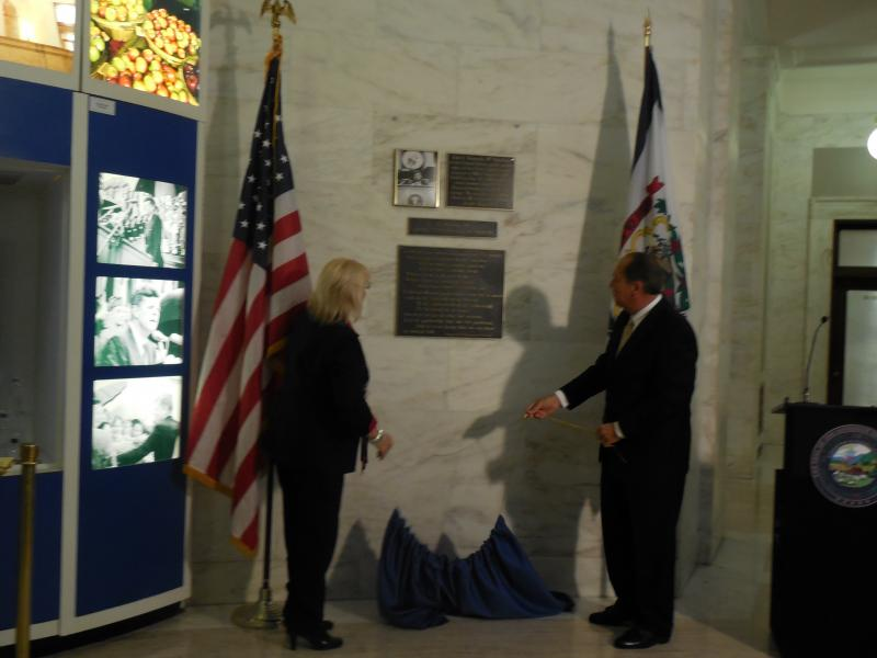 First Lady Joanne Jaeger Tomblin and Governor Earl Ray Tomblin reveal the plaque dedicated to President John F. Kennedy in the state Capitol.