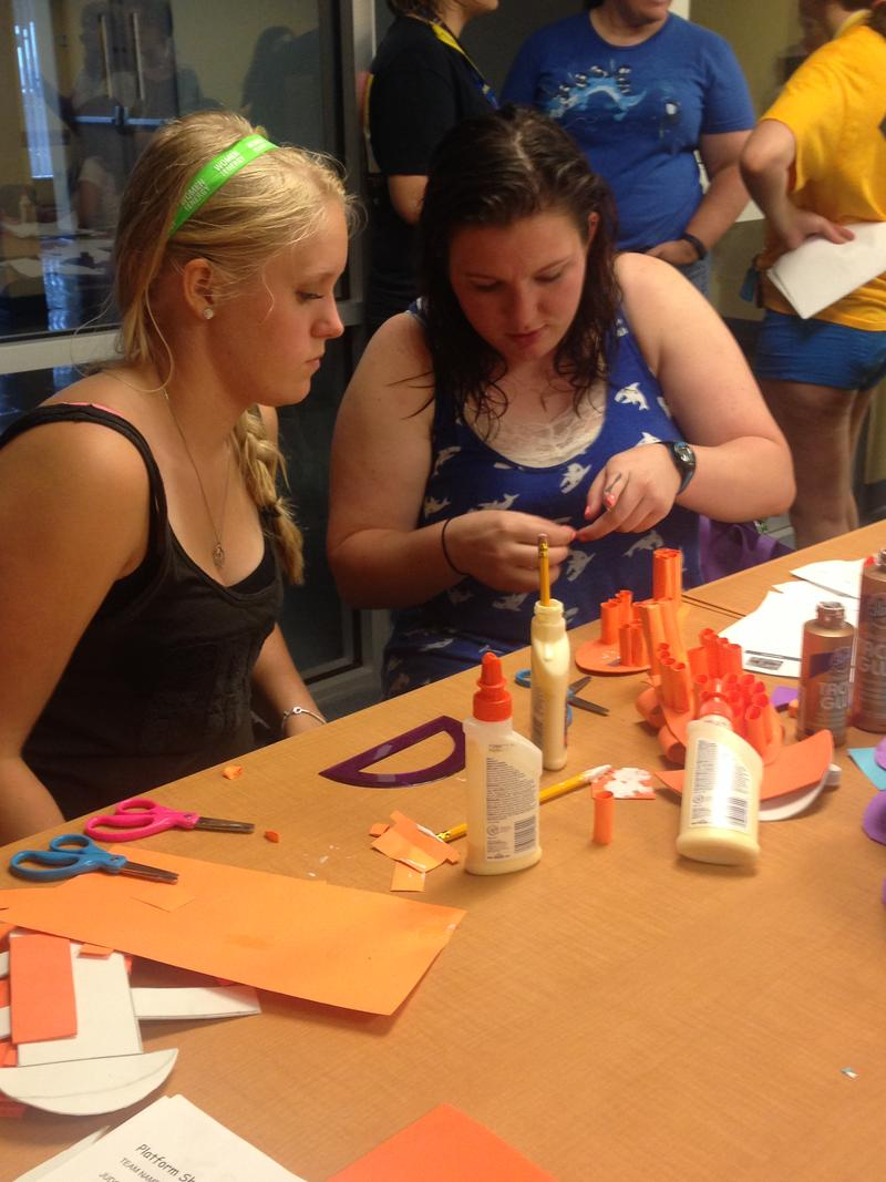 Camp counselor Kaylah Bovard (right) helps a camper finish up her paper shoes for a biomechanical engineering competition.