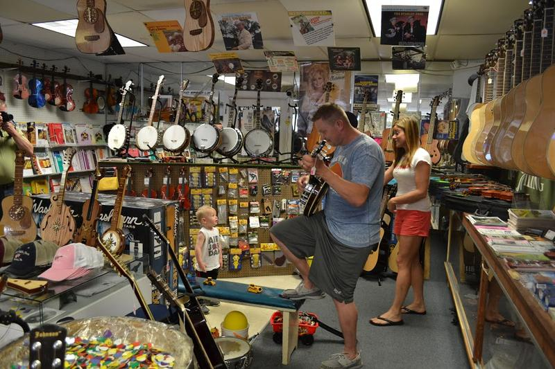 Stevia Barr, Banjo Player, plays for his son inside their family's fiddle shop in Galax, Virginia