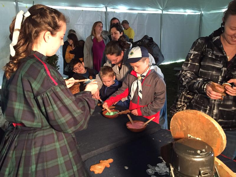Colleen Moran (left) helps children decorate gingerbread cookies, a common Christmas tree ornament during the Civil War