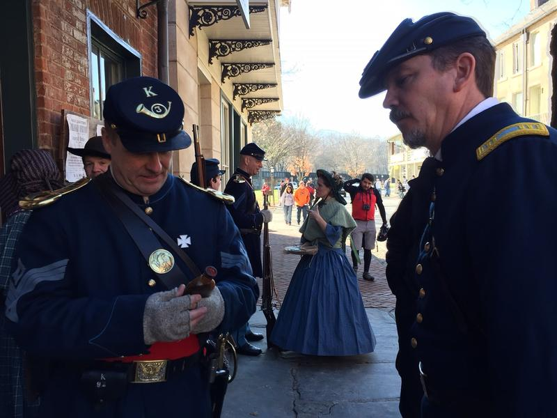 Two reenactors portraying Union soldiers discuss the contents of a box mailed to a fellow soldier stationed in Harpers Ferry