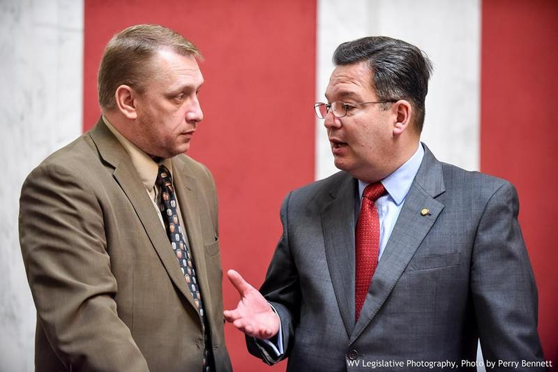 House Education Chair Del. Paul Espinosa speaking with Del. Larry Faircloth during a recent floor session.