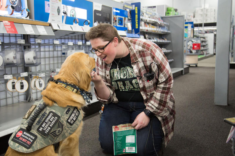 Rachel Gregory talks to her service dog, Missy, at Best Buy.