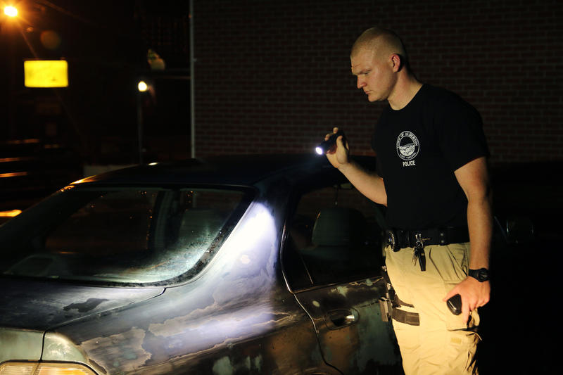Patrolman Mac Brackenrich of the Alderson Police Department looks over a vehicle parked in an alley way. City officials in Alderson and White Sulphur Springs are enforcing a curfew to stave off potential theives and looters.