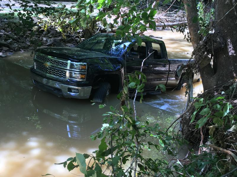 A truck that was parked outside of a nearby home is stuck on a concrete wall in a creek.