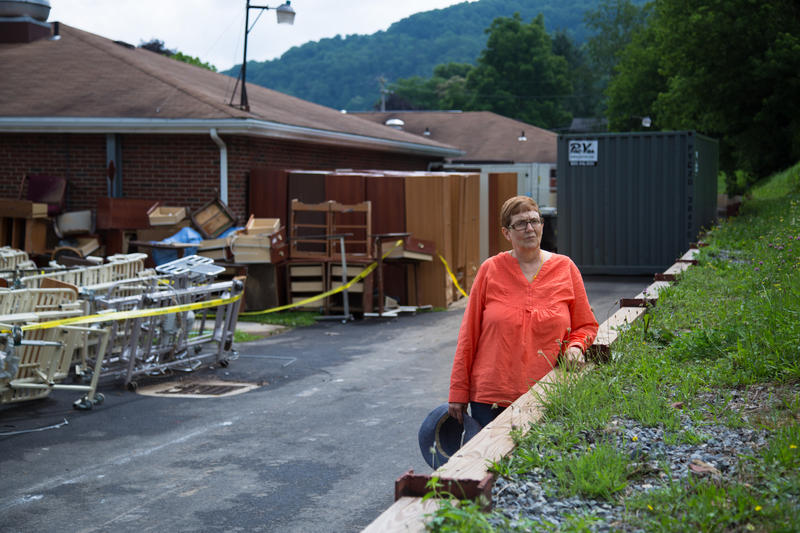 Former nursing home physical therapy assistant Kathleen Curry stands by the retaining wall behind the Nicholas County Nursing Home. During the evacuation, patients had to be lifted out of the water and onto the bank.