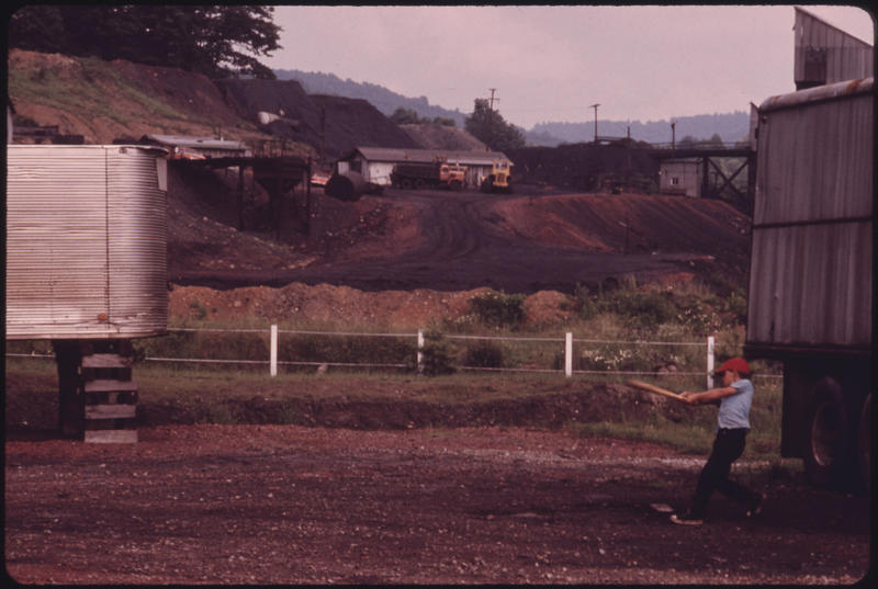 A boy in Raleigh County takes a swing at baseball while behind him is a mine site