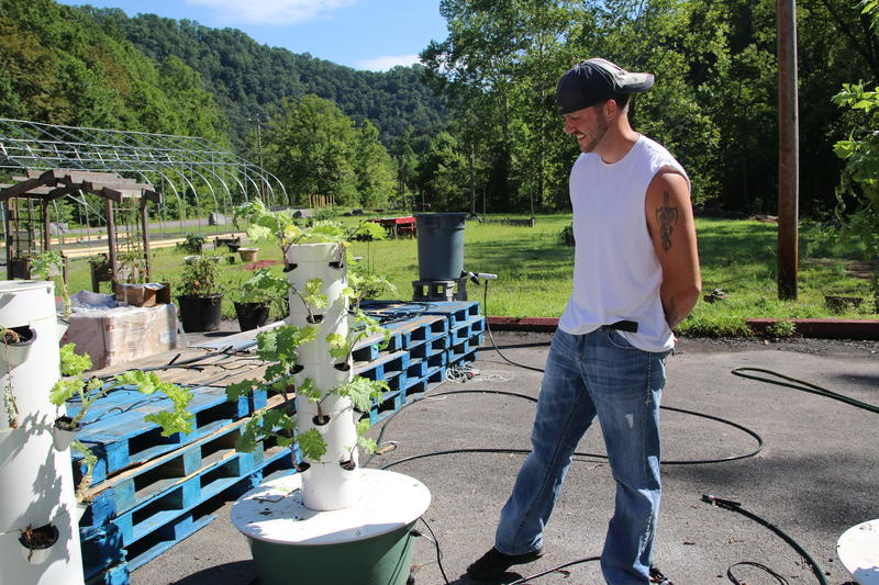 Joel McKinney stands beside a hydroponic tower that is part of his farm outside the Five Loaves Food Pantry
