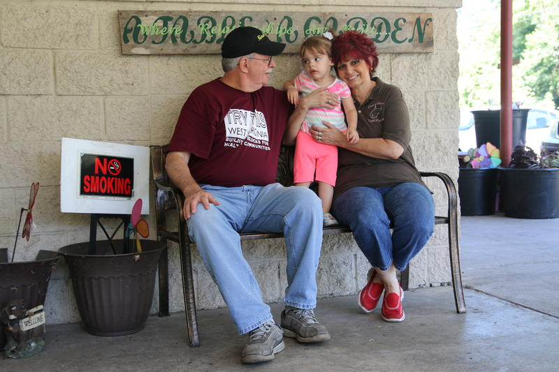Bob and Linda McKinney, and their granddaughter Nora, sit outside the Five Loaves Two Fishes Food Pantry