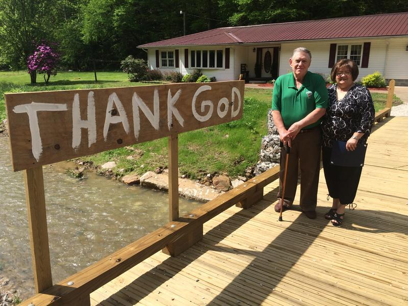 Chuck and Carol Adkins stand on the wooden decking of the bridge Mennonites designed and built for them in the wake of July 2015 flooding.