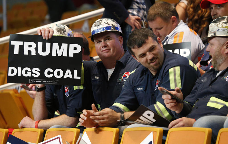 A group of coal miners hold Trump signs as they wait for a rally with Republican presidential candidate Donald Trump.