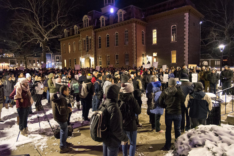 Community members gather at Woodburn Circle for a vigil to support those affected by the executive order.