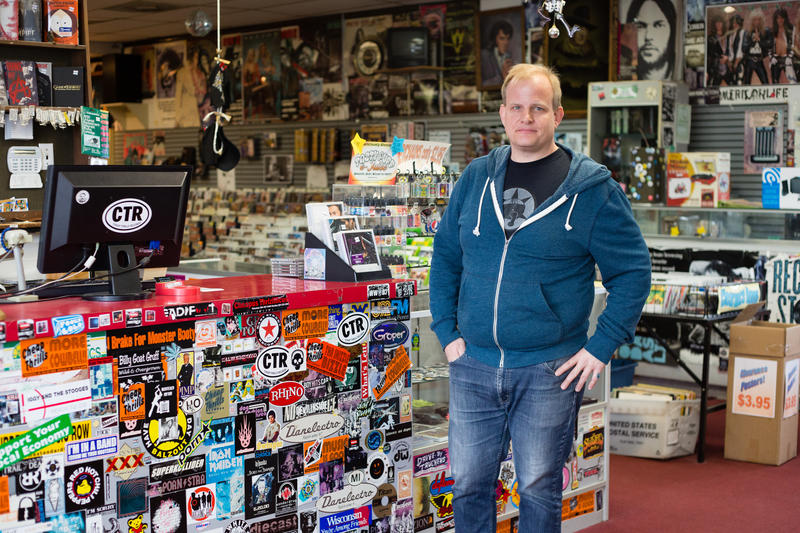 Wyatt Lilly stands in his Princeton, WV, record shop. He has been self-insured since the 1990s and says that the ACA helped lower his premiums and deductibles.