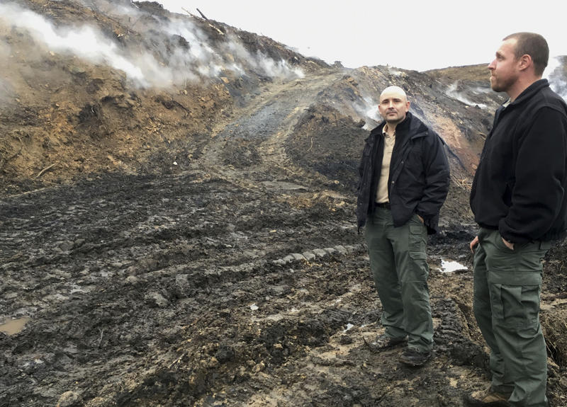 Rob Rice, left, chief of the West Virginia Office of Abandoned Mine Lands and Reclamation, and planner Jonathan Knight check on the smoldering underground fire at a long-abandoned coal mine in Preston County, W.Va.