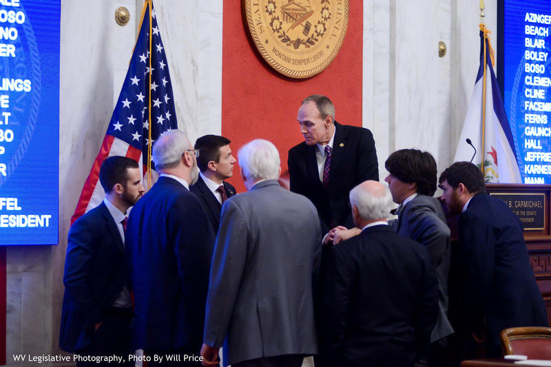 Members of the Senate's learship tema gather around Senate President Mitch Carmichael during the debate over the proposal.