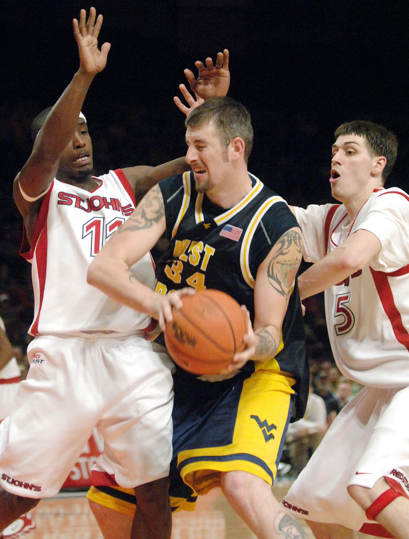 West Virginia's Kevin Pittsnogle, center, is defended by St. John's Phil Missere, right, and Cedric Jackson, left, in the second half of their Big East Conference college basketball game in New York, Sunday, January 29, 2006.