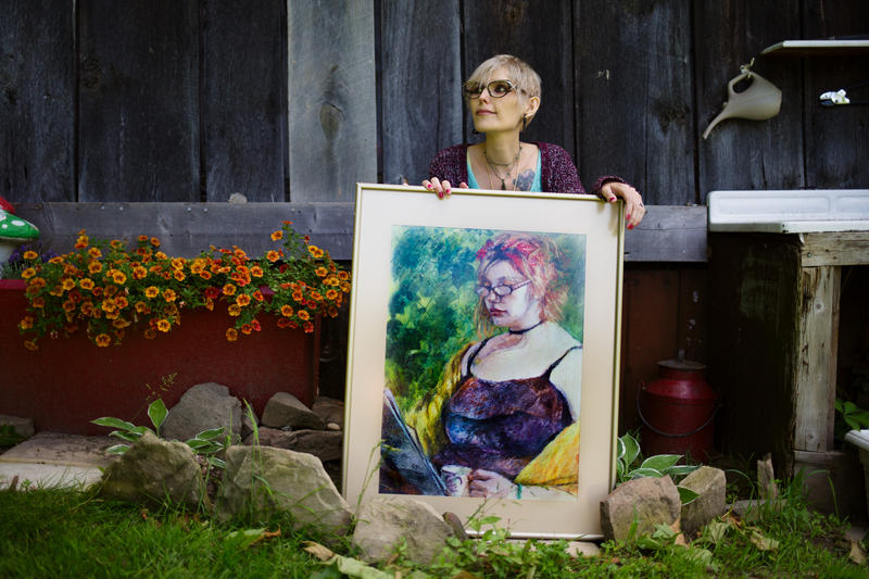 Lacie Wallace sits in her backyard holding a painting done of her when she was healthy, but overweight. In the past year she has lost about 100 pounds and no longer recognizes the person in the mirror.
