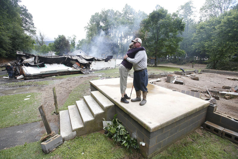 In this June 24, 2016 file photo, Jimmy Scott gets a hug from Anna May Watson, left, as they clean up from severe flooding in White Sulphur Springs, W.Va.
