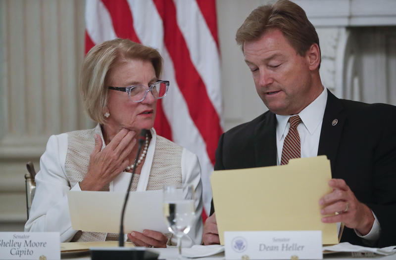 Sen. Shelley Moore Capito, R-W.Va., left, and Sen. Dean Heller, R-Nev., look over documents during a luncheon with President Donald Trump, Wednesday, July 19, 2017, in the State Dinning Room of the White House in Washington.