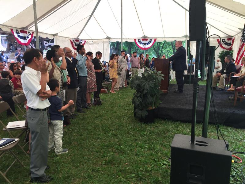 All 19 new United States citizens stand and take the Oath of Allegiance.