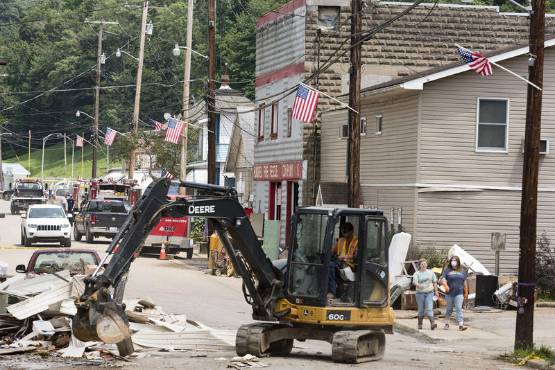 National guardsmen and volunteers clean up flooding debris Tuesday, Aug.1, on Pennsylvania Ave. in Hundred, W.Va.