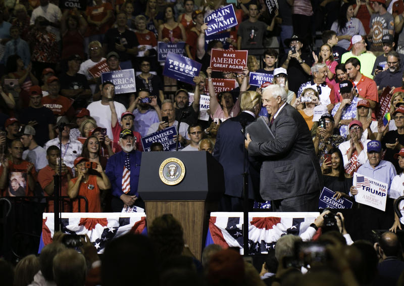 Gov. Jim Justice hugs Pres. Donald Trump before announcing he'd switch parties in at a Huntington rally last week.