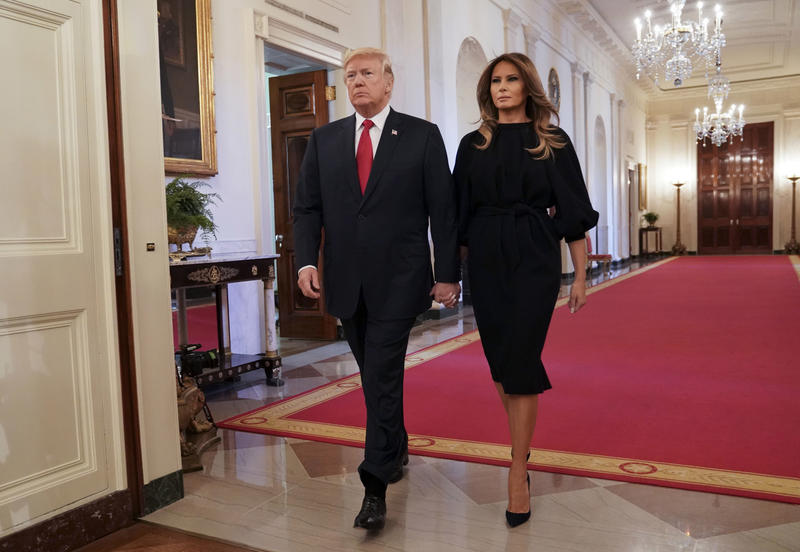 President Donald Trump and First Lady Melania Trump walk in to speak on the opioid crisis in the East Room of the White House in Washington, Thursday, Oct. 26, 2017.
