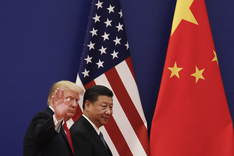 U.S. President Donald Trump waves next to Chinese President Xi Jinping after attending a business event at the Great Hall of the People in Beijing, Thursday, Nov. 9, 2017.