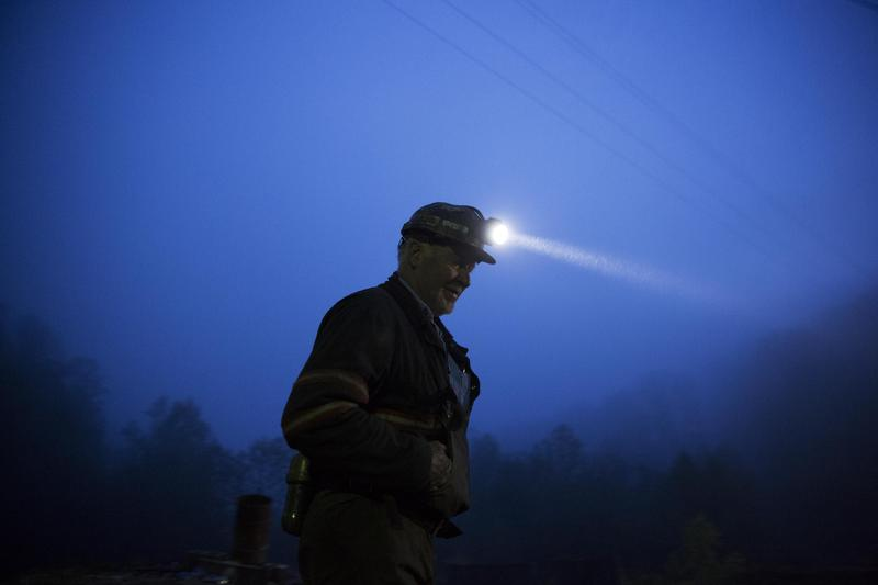 In this Thursday, May 12, 2016 photo, coal miner Scott Tiller prepares to head into an underground mine less than 40-inches high at dusk in Welch, W.Va.