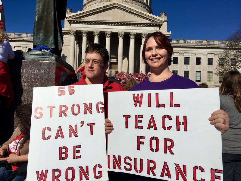 Teachers John and Kerry Guerini of Fayetteville, West Virginia, hold signs at a rally at the state Capitol in Charleston, W.Va., Monday, Feb. 26, 2018.
