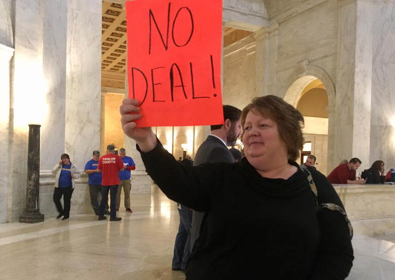 Sherman High School special needs teacher's aide Belva Perry holds up a sign Wednesday, Feb. 28, 2018, at the state Capitol in Charleston, W.Va. Thousands of teachers showed up again at the Capitol to voice their frustrations over pay and benefits.