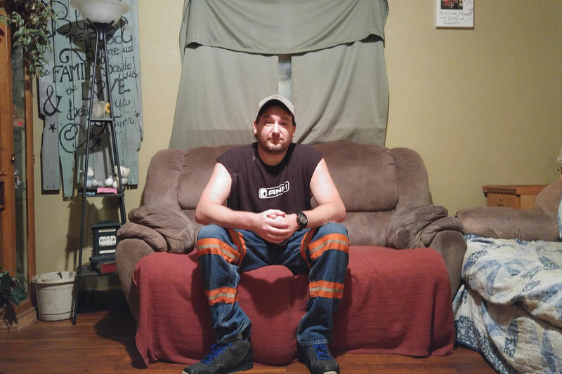 Mackie Branham wears reflective mining pants in his home in Elkhorn City, Ky. Branham has advanced stage black lung and was forced to quit mining earlier this year.