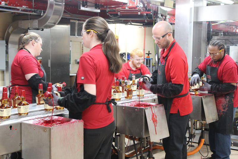 Maker's Mark workers hand dip bottles into red wax.