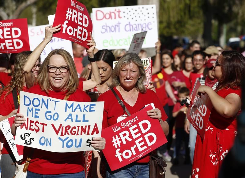 Arizona teachers and education advocates march at the Arizona Capitol protesting low teacher pay and school funding Wednesday, March 28, 2018, in Phoenix.