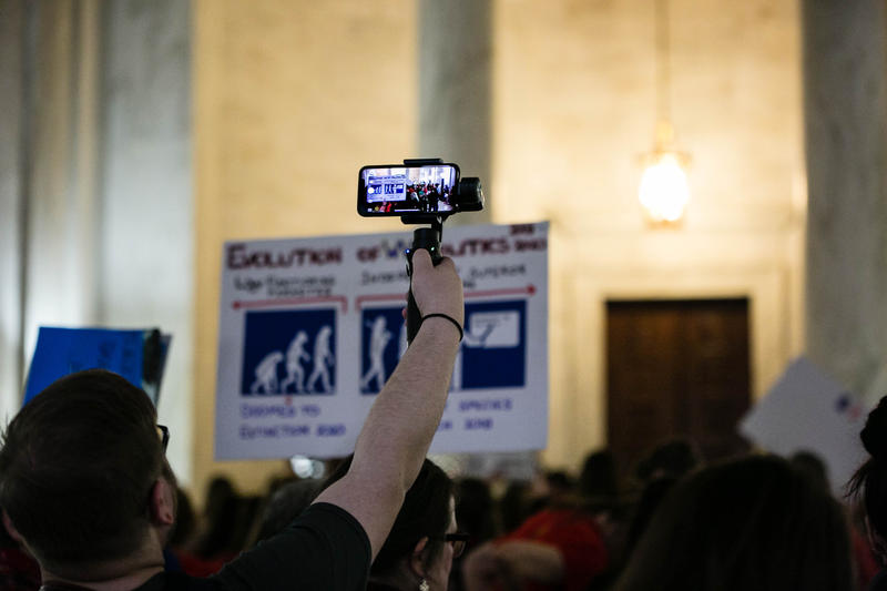 Teachers hold up signs and cell phones during the March strike at the Capitol