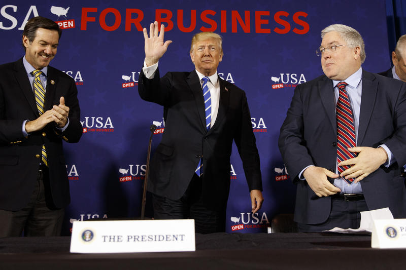 Rep. Evan Jenkins, R-W.Va., left, and West Virginia Attorney General Patrick Morrisey, right, watch as President Donald Trump arrives for a roundtable discussion on tax policy, Thursday, April 5, 2018, in White Sulphur Springs, W.Va.